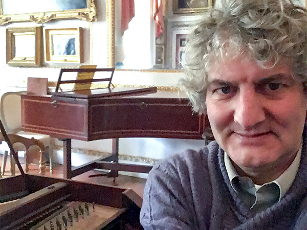 Tim Hendy tuning at the Cobbe Collection surrounded by antique pianos